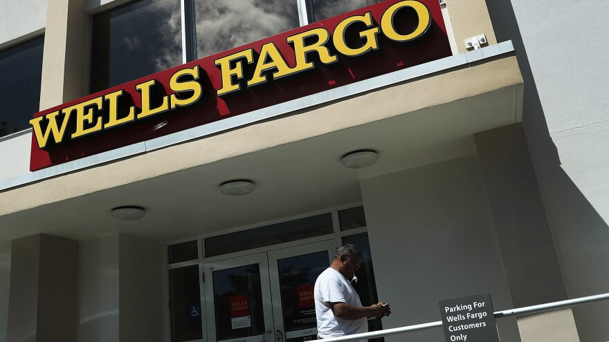 A Wells Fargo executive's departure with large stock and options holdings has sparked questions, after the division she ran incurred $185 million in penalties.