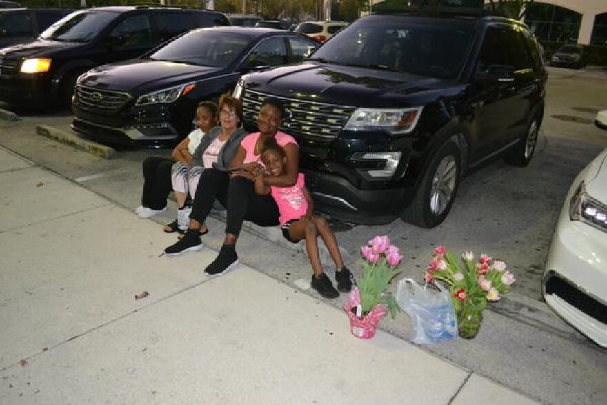 From left, Shoshanna Campbell, Fawn Patterson, Joedonna Harrison and her daughter, Jayanna, sit on a concrete block in the parking lot of Broward Health Medical Center on Feb. 14. They were kept from visiting loved ones being treated inside because of a lockdown related to the shooting.