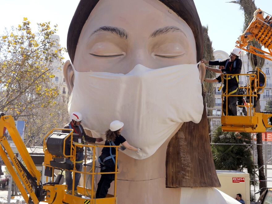 The World Health Organization called the COVID-19 viral disease a pandemic Wednesday. Here, workers in Spain place a medical mask on a figure that was to be part of the Fallas festival in Valencia. The festival has been canceled over the coronavirus outbreak.