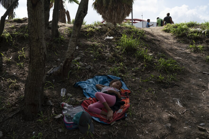 A child sleeps at the encampment area where hundreds of asylum seekers are staying near the Gateway International Bridge.