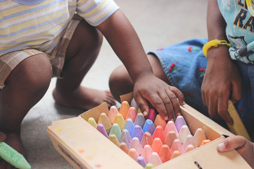 Two Children crouch on the ground near a box of colorful chalk.