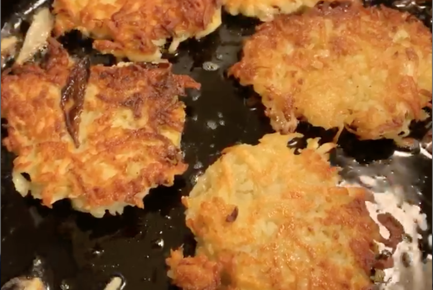 Brett Rothfeld fries latkes in a cast iron pan in his home in Oregon.