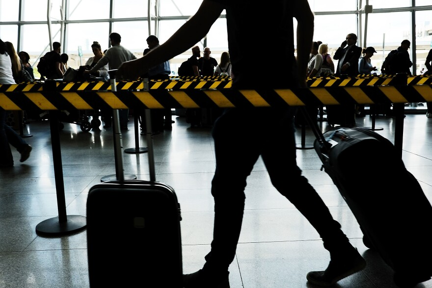 People arrive at John F. Kennedy international airport following an announcement by the Supreme Court that it will take President Donald Trump's travel ban case later in the year on Monday in New York City.