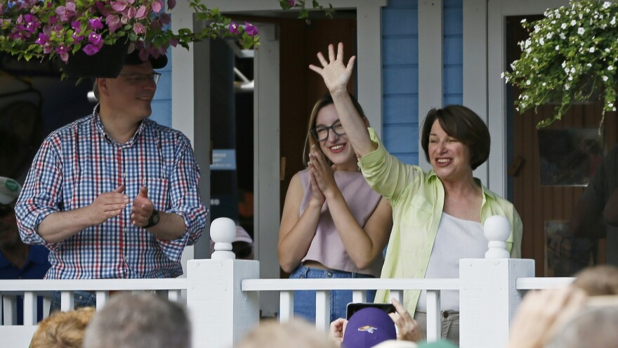 Minnesota Sen. Amy Klobuchar, D-Minn., waves to fair goers from her fair booth at the Minnesota State Fair. With her, left, is her husband John and daughter Abigail.