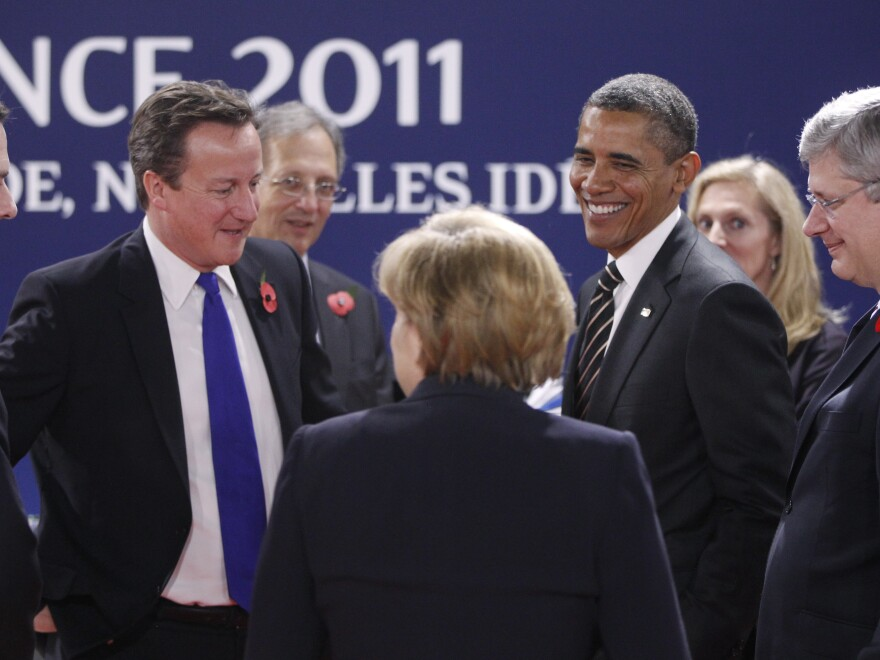 Jon Cunliffe, center, then Britain's International Economic and EU Advisor, stands behind Prime Minister David Cameron in November 2011 as he speaks with U.S. President Barack Obama, and German Chancellor Angela Merkel at a G20 Summit. The Guardian reports that Cunliffe's secretary accidentally leaked to the paper Great Britain's plan for a possible exit from the European Union.