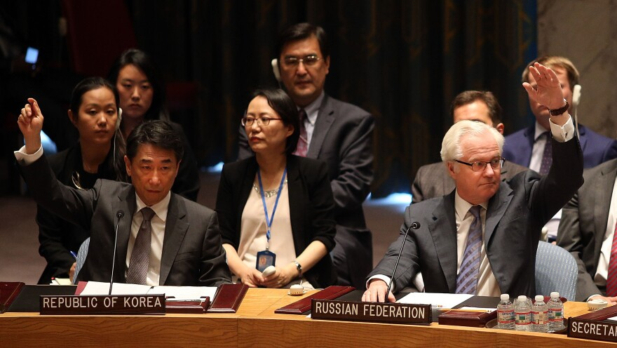 Russian Ambassador to the United Nations Vitaly Churkin votes for a U.N. Security Council draft resolution demanding full access for investigators at the Malaysia Airlines crash site in eastern Ukraine.