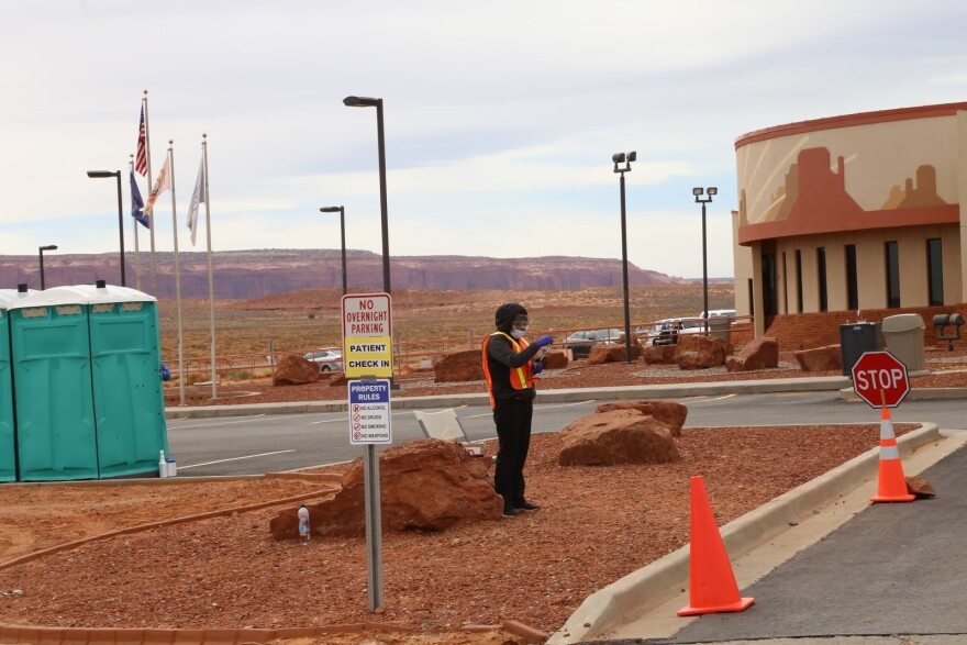 A woman in personal protective equipment stands in the driveway of a health clinic in Monument Valley.