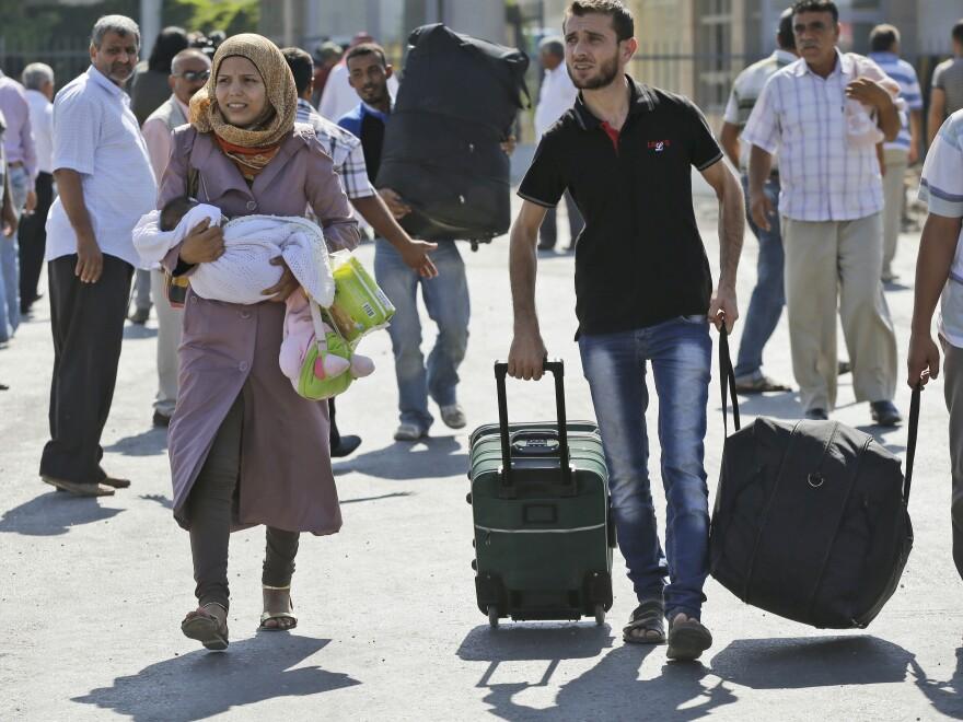 Syrian refugees pass through the Turkish Cilvegozu gate border on Sunday.