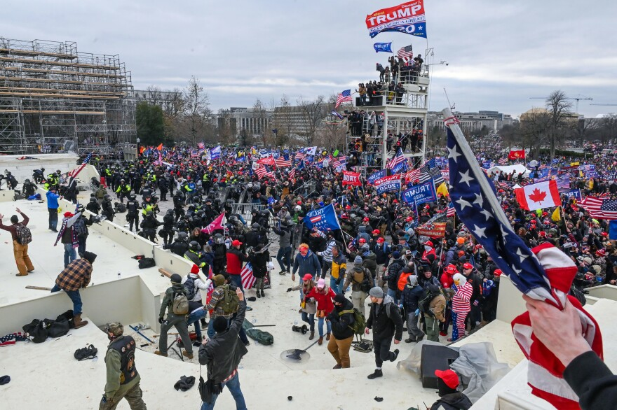 Trump supporters clash with police and security forces as they invade the Inauguration platform.