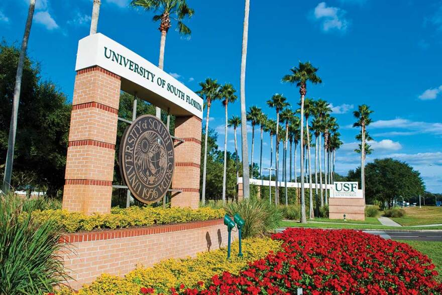 """A picture of the brick sign reading """"USF"""" with flowery landscaping around it."""
