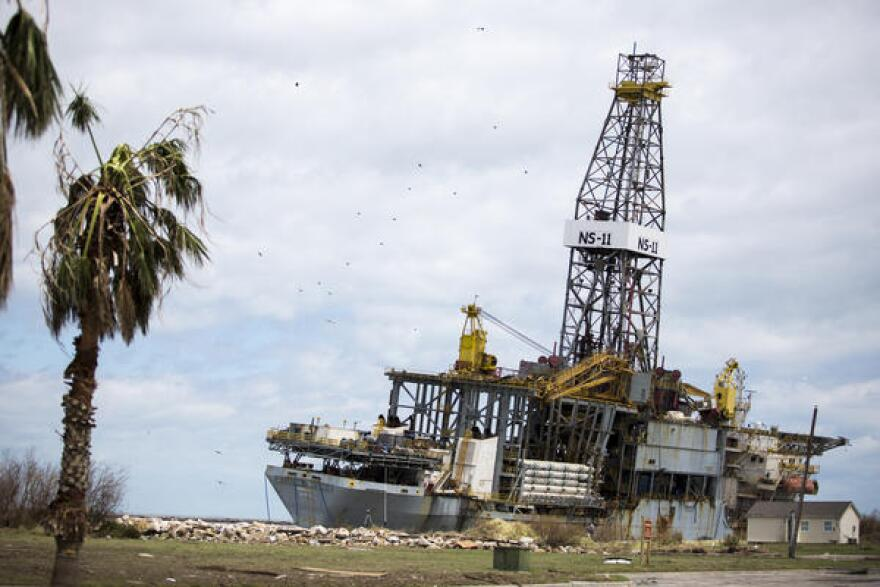 An oil drilling ship is beached onshore.