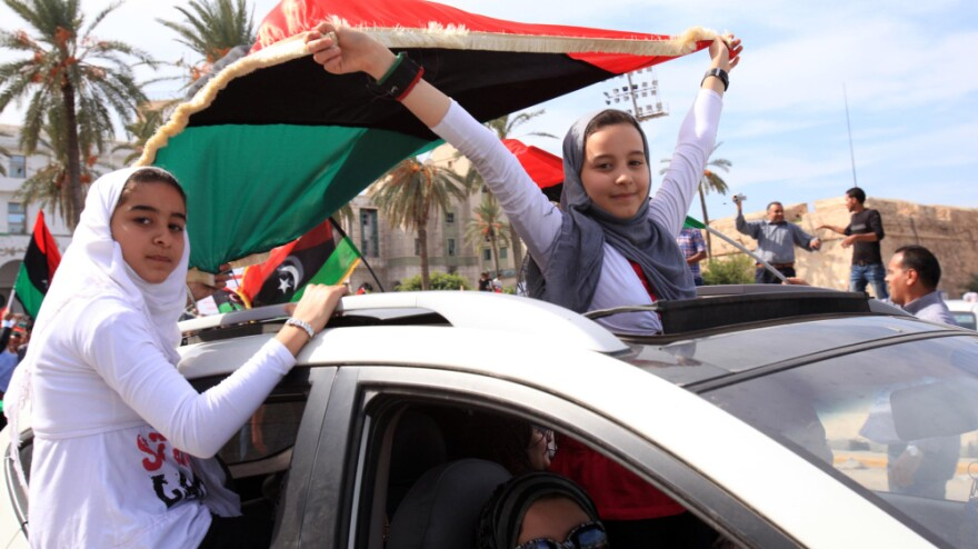 <p>Libyan girls wave flags of the Transitional National Council as they ride through the streets of Tripoli following word of Moammar Gadhafi's death. </p>