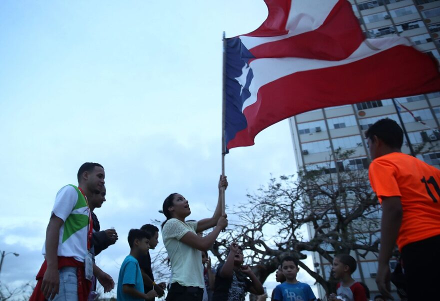 A Puerto Rican flag is waved outside the Torres de Francia complex as people deal with the aftermath of Hurricane Maria on Oct. 1, 2017 in San Juan, Puerto Rico. (Joe Raedle/Getty Images)