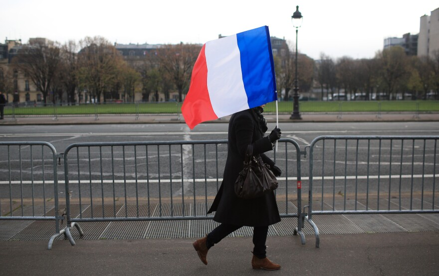 A woman carries a French flag during a ceremony in Paris on Friday honoring those killed in the Nov. 13 attacks. French President Francois Hollande has encouraged the French people to display flags, something they don't often do.