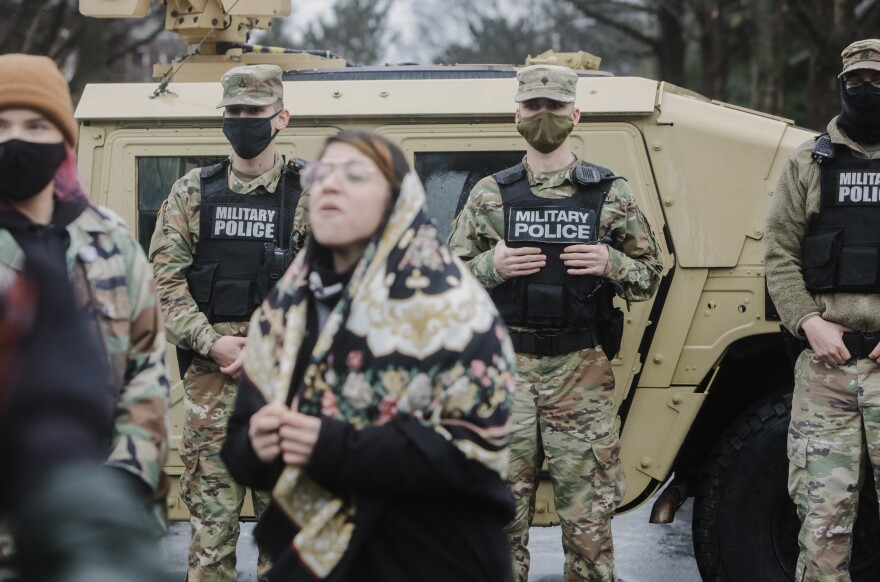 A demonstrator shouts slogans in front of members of the National Guard outside the Kentucky State Capitol in Frankfort, Kentucky.