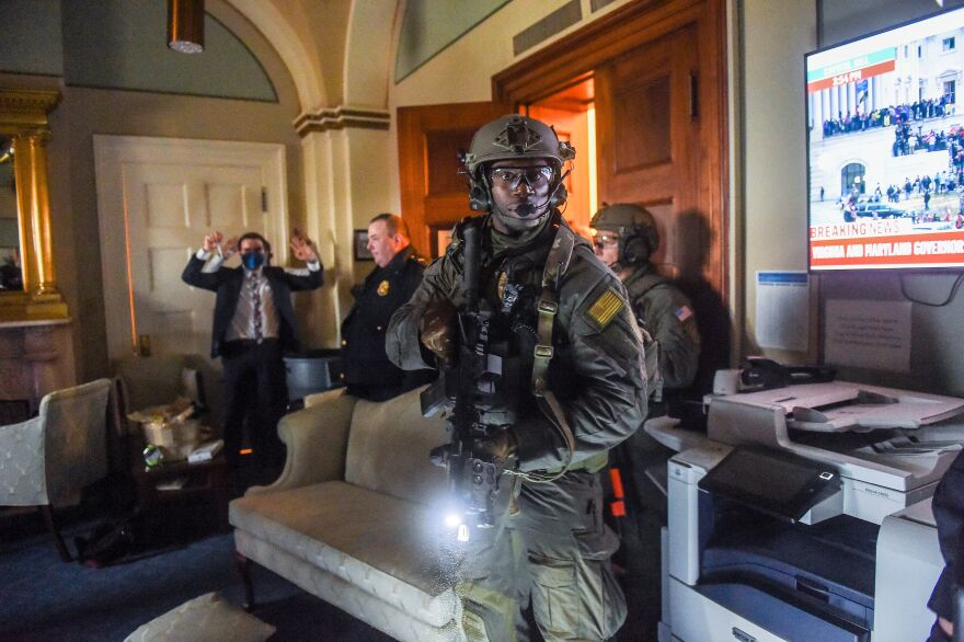 A Congress staffer holds his hands up while Capitol Police Swat team check everyone in the room as they secure the floor of Trump supporters who mobbed the Capitol building.