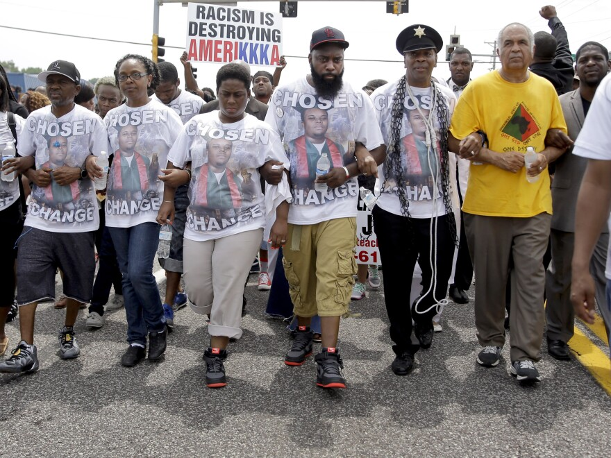 Michael Brown Sr. (center) leads a march in remembrance of his son, Michael Brown, on Sunday in Ferguson, Mo. It has been exactly one year since Michael Brown was shot and killed by police officer Darren Wilson.