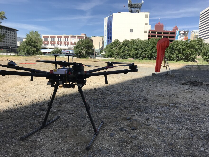 A drone sits in an empty dirt lot, waiting for a nearby drone pilot to begin its flight. The drone will fly beyond where the pilot can see to another lot two blocks away.