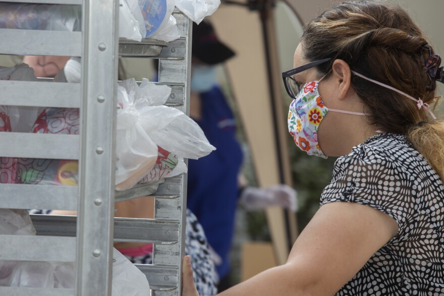 a woman wearing a cloth mask pulls bags of food off a metal cart.