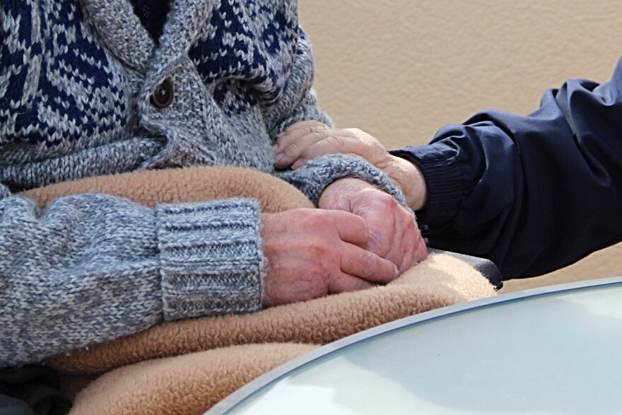 A picture of a nurse holding an elderly person's hand.