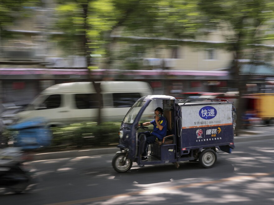 A private delivery company's courier drives his delivery cart in a residential area in Beijing in June.
