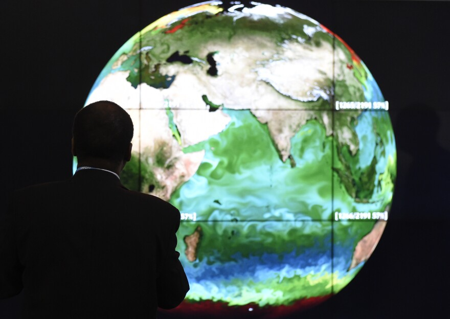 A conference attendee looks at a projection of the Earth on Monday, the opening day of the COP 21 United Nations conference on climate change, in Le Bourget, on the outskirts of Paris.