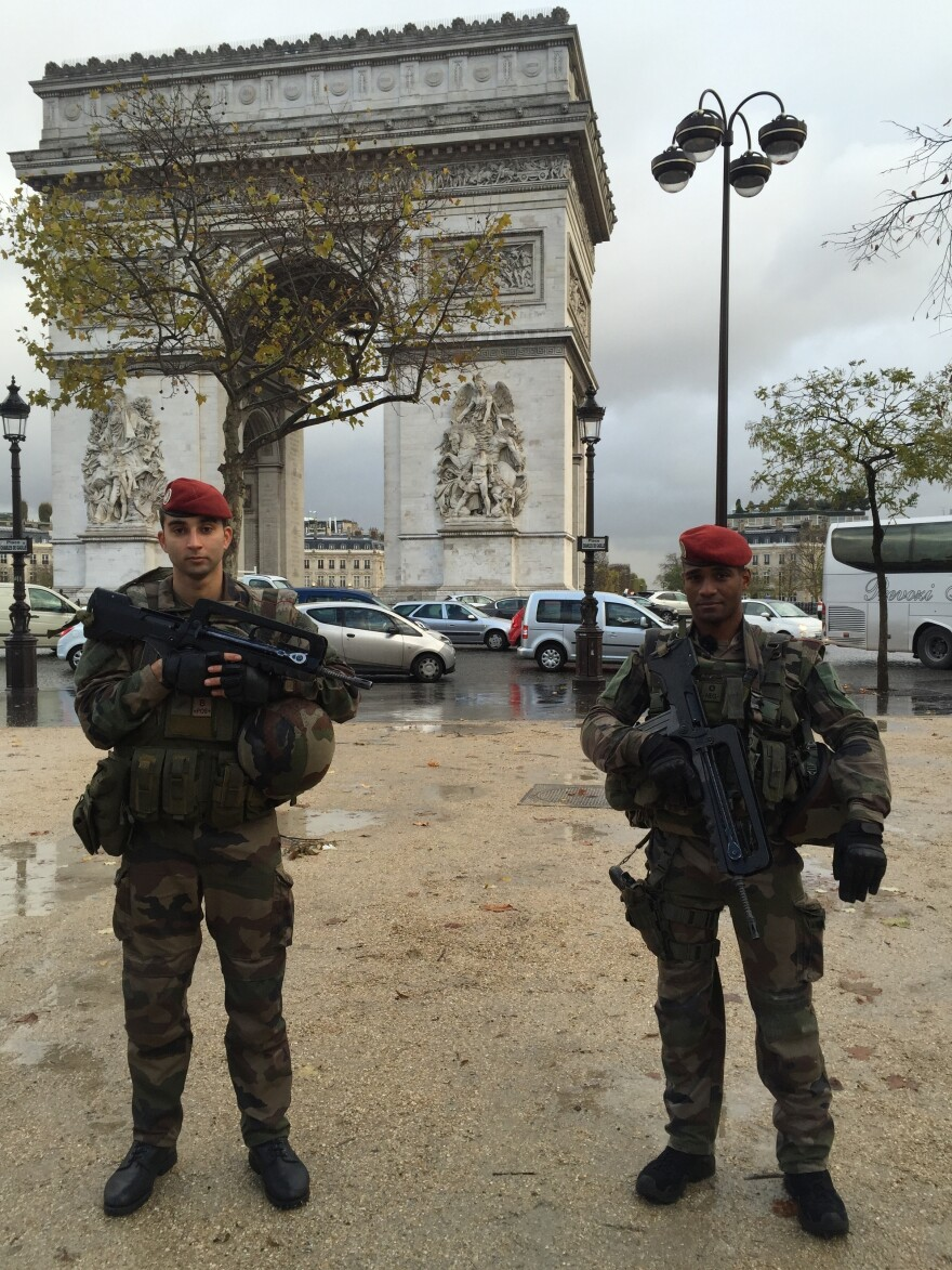 Two French soldiers in front of the Arc de Triomphe.