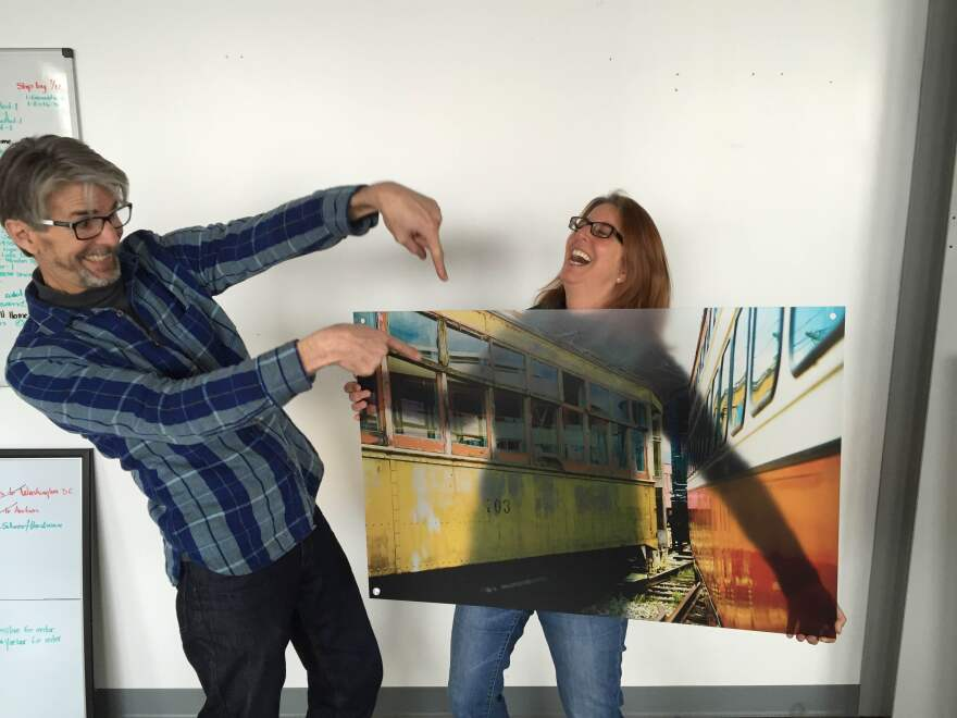 """Tom and Vicki holding """"Trains"""" on 2x3 transparent acrylic shot at the Columbus train museum"""