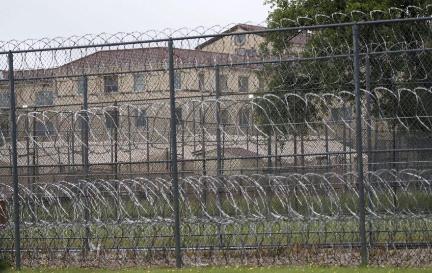 Wire fences near buildings of the Federal Medical Center prison in Fort Worth, Texas, Saturday, May 16, 2020. Hundreds of inmates inside the facility have tested positive for COVID-19. (LM Otero/AP)