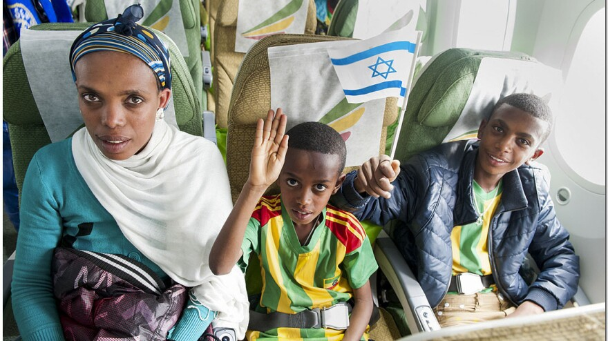 A boy waves the flag of his new homeland on the last flight of organized, large-scale emigration of Ethiopian Jews to Israel.