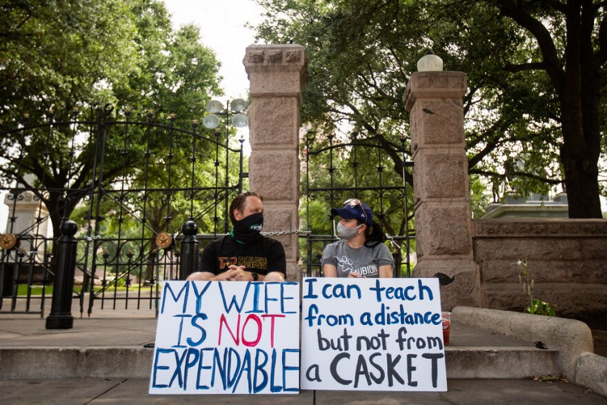 Weston and Lorri Boyd hold signs outside the Capitol on Wednesday.
