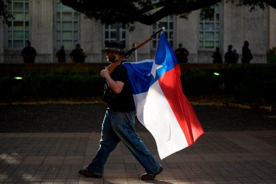 A man walks with a rifle with a Texas flag attached to it during a Police Appreciation rally at the City Hall in Houston, Texas.