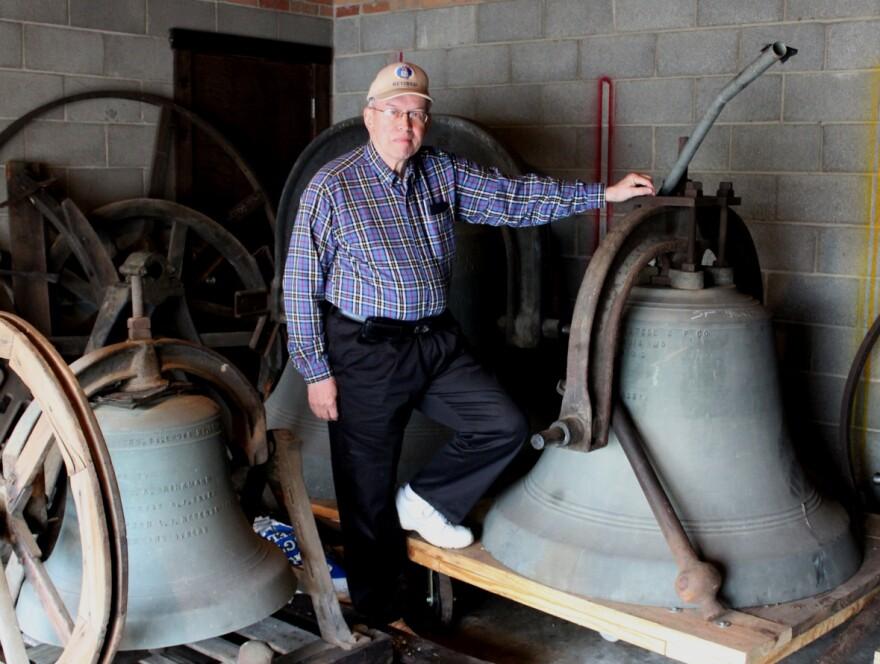 Carl Zimmerman standing between two large bronze bells in a storage garage.