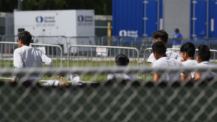 Migrant children run around a track outside at the Homestead Temporary Shelter for Unaccompanied Children in Homestead, Fla. Shelters that house these children are reaching capacity and the federal government is now working to speed releases to sponsors.