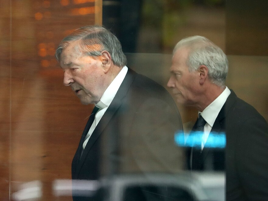 Cardinal George Pell (left) leaves Melbourne Magistrates' Court on Wednesday in Melbourne, Australia.