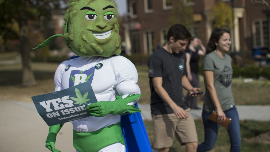 Buddie, the mascot for the pro-marijuana legalization group ResponsibleOhio, greets passing college students at Miami University last month in Oxford, Ohio.