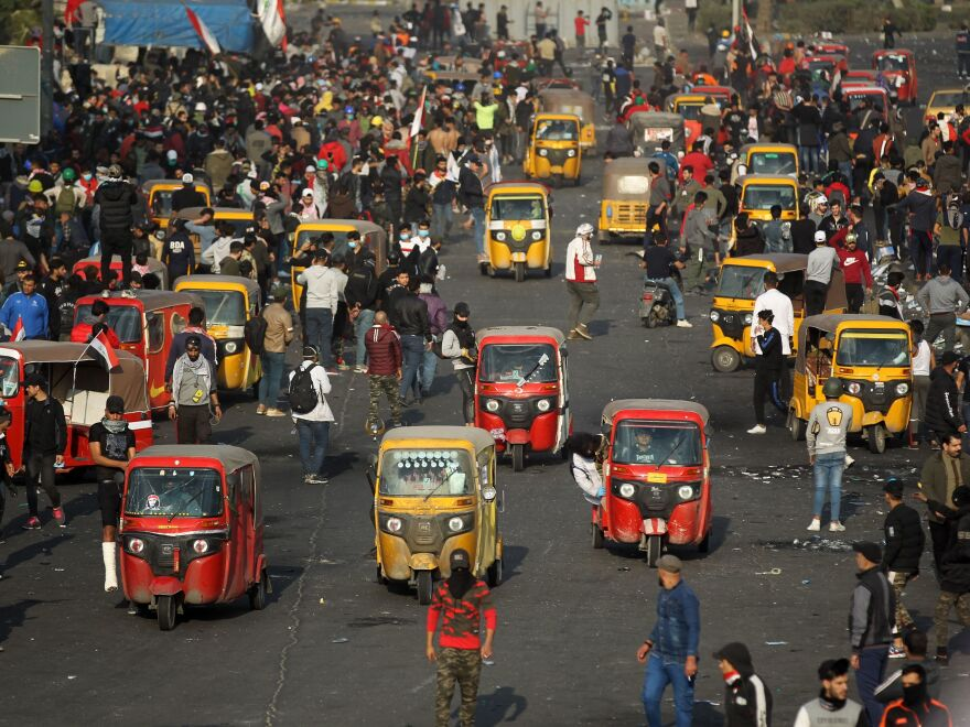 Iraqi protesters and tuk-tuk drivers gather amid clashes with riot police following a demonstration in Baghdad on Monday.