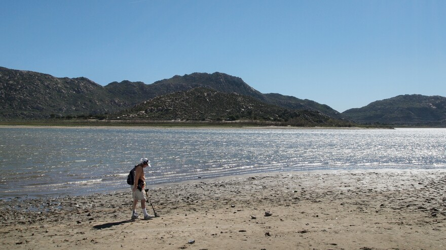 "Marty Gabriel, a retired truck driver, passes his metal detector over the exposed sand at California's Lake Perris. Gabriel has been visiting the lake for 25 years. ""We definitely need rain,"" he says."