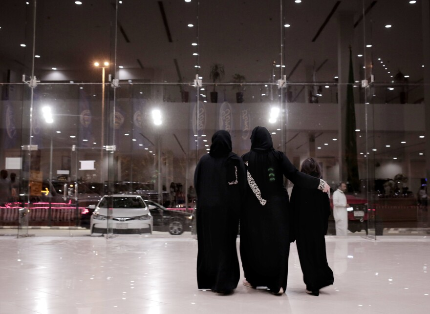 Women leave after looking at cars at the Al-Jazirah Ford showroom in Riyadh on June 21.