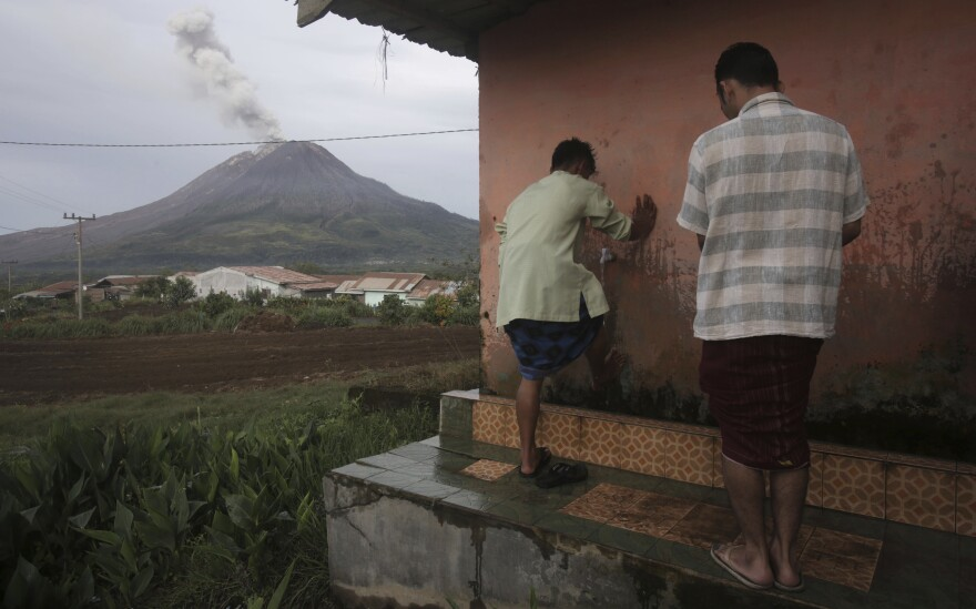 Young men wash up before performing their Eid al-Fitr prayer at a mosque near Mount Sinabung, an active volcano in Indonesia.