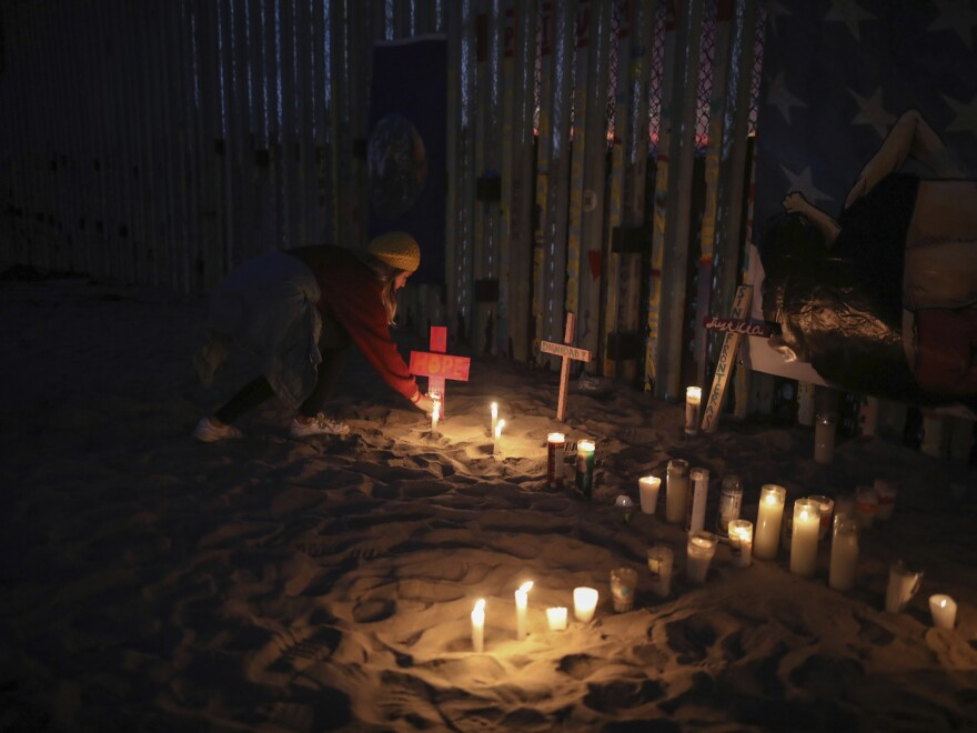 Candles are placed next to the U.S.-Mexico border fence earlier this year in Tijuana, Mexico, in memory of migrants who have died during their journey toward the U.S.
