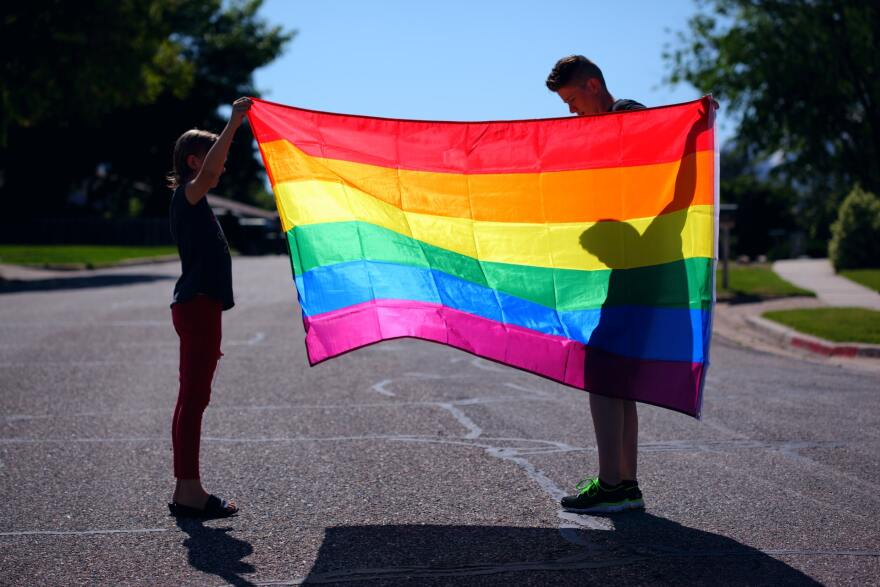A parent and child holding a rainbow pride flag in the middle of an empty street.