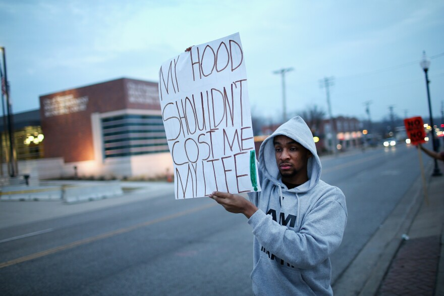 A demonstrator protests in front of the police station in Ferguson, Mo., on Thursday.