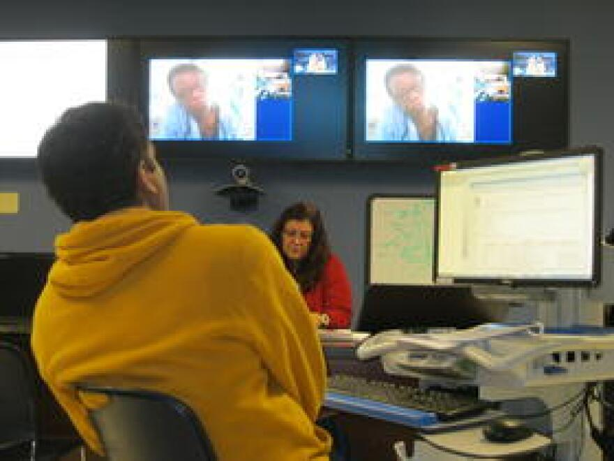 Dr. Shailesh Garg (foreground) in Miami advises Dr. Kathleen Charles (on video screens) in Haiti.