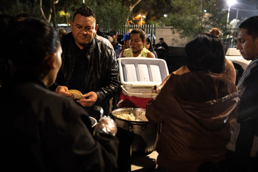 With the help of his family and employees, José Aguilar delivers five containers of a hearty Honduran-style chicken stew to the caravan.
