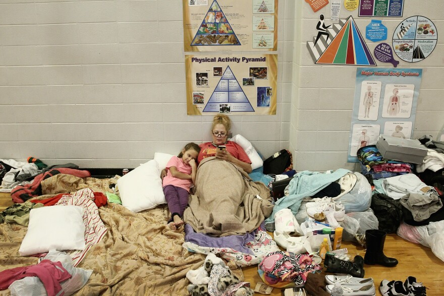 Christine Garcia relaxes with her 8-year-old daughter Mia in the Channelview High School gym. It's been turned into an evacuation shelter for victims of flooding from Harvey.