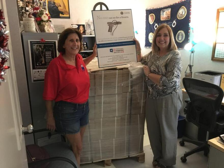 Barbara Markley and Gloria Lewis stand with the military-sized shipment of gun locks in Lewis's office.