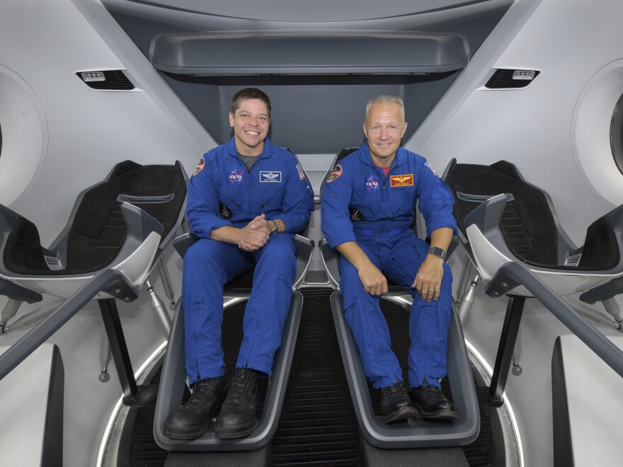 NASA astronauts Bob Behnken, left, and Doug Hurley, are assigned to fly on the first test flight of SpaceX's Crew Dragon May 27. Here, they pose inside a mockup of the spacecraft in Houston in 2018.