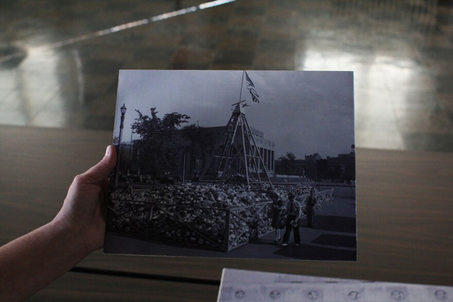 Lynnea Magnuson holds a photo showing scrap metal drives held outside Soldiers Memorial during WW II.