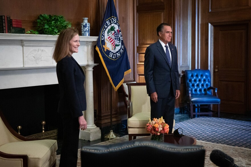 A photo of Mitt Romney and Amy Coney Barrett.